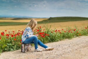 Girl with a suitcase sitting by empty road